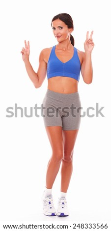 Satisfied young woman winning sports against white background - copyspace - stock photo