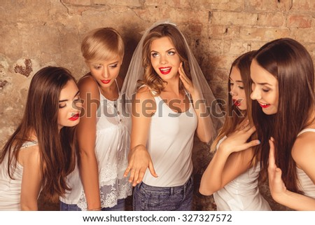 Satisfyed cute bride showing her bridesmaids wedding ring - stock photo