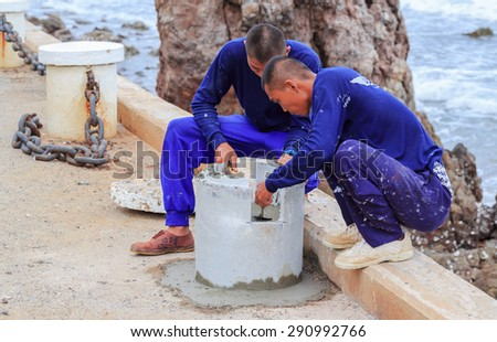 "SATTAHEEP CHONBURI-JUNE,27:Unidentified men are fixing the cement pole that located along the road by the sea.This is time to maintenance for good view of ""TEUY GHAM"" beach.THAILAND JUNE,27 2015"
