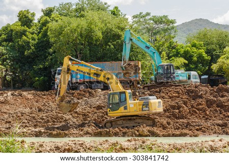 SATTAHIP , THAILAND - AUGUST 5, 2015 : Backhoe and truck on the construction at digging the pit. The work of construction machinery in a quarry , Thailand on August 5, 2015 - stock photo