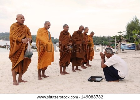 SATUN, THAILAND - APRIL 02; Unidentified monks collect alms and offerings at Lipe island Satun, Thailand on April 02, 2010. This procession is held every day in the early morning. - stock photo