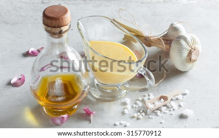 Sauce Aioli  homemade from olive oil, garlic and salt in glass sauceboat on the rustic white wooden table horizontal - stock photo