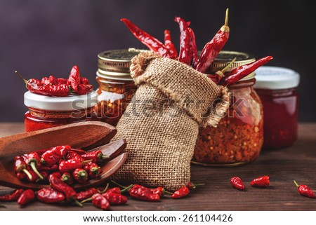 sauce many different peppers in glass container - stock photo