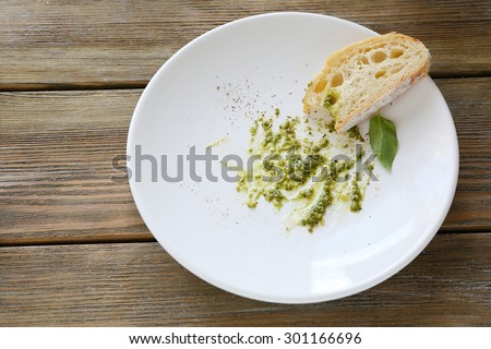 Sauce Pesto on plate with slice of bread, food - stock photo