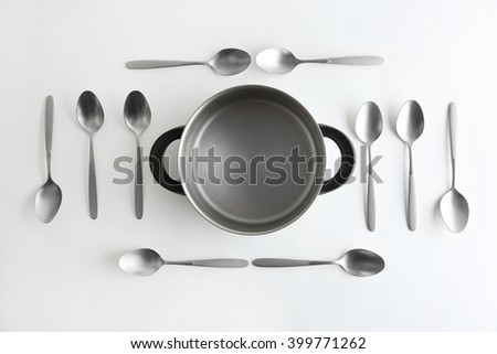 Saucepan and silver spoons, top view - stock photo