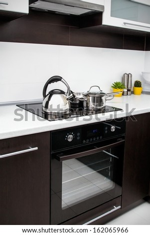 Saucepan, kettle and frying pan in modern kitchen - stock photo