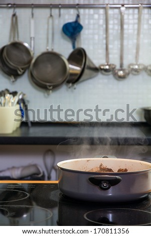 Saucepan with a meat on the plate - stock photo