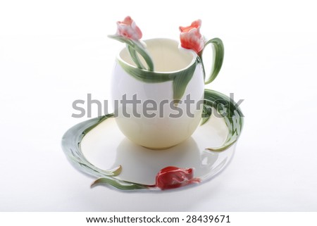 Saucer, cup and spoon decorated with red flower and green color - stock photo
