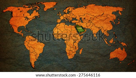 saudi arabia flag on old vintage world map with national borders - stock photo