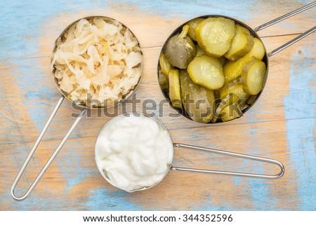 sauerkraut, cucumber pickles and yogurt - popular probiotic fermented food - three measuring cups against rustic wood - stock photo
