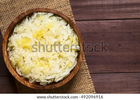 Sauerkraut in wooden bowl, photographed overhead on dark wood with natural light (Selective Focus, Focus on the top of the sauerkraut)
