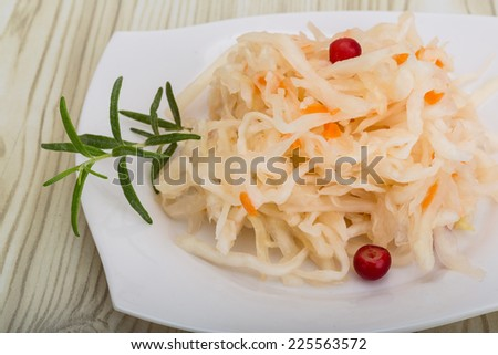 Sauerkraut with berries in the bowl on wooden background - stock photo