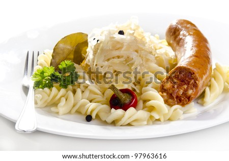Sauerkraut with noodle and home made sausage on a white plate - stock photo