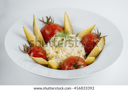 sauerkraut with pickled cucumbers, tomatoes and dill on a white plate - stock photo