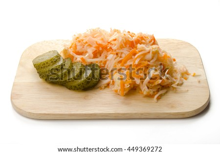 Sauerkraut with pickles on a wooden cutting board isolated - stock photo