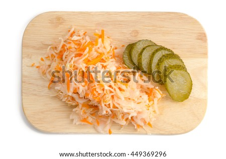 Sauerkraut with pickles on a wooden cutting board isolated. Top view. - stock photo