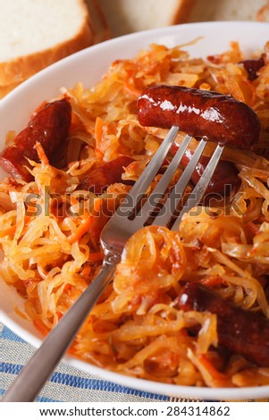 sauerkraut with sausage macro in a white plate. vertical - stock photo