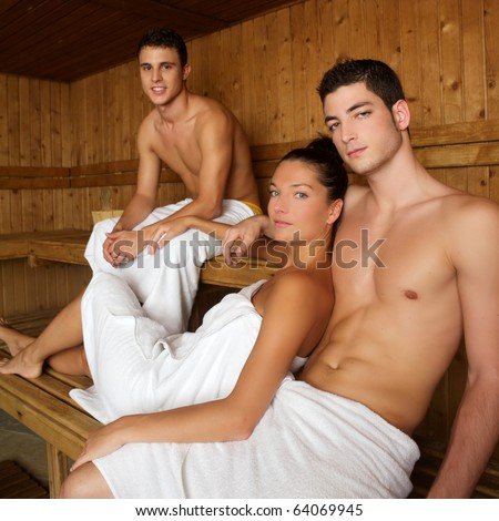 Sauna spa therapy beautiful young people group in warm wood room white towel - stock photo