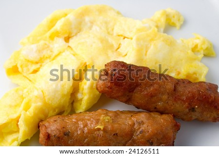 Sausage and eggs on plate - stock photo