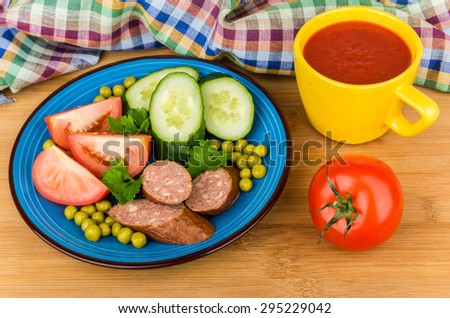 Sausage and vegetables in blue plate, tomato juice in yellow cup on wooden table