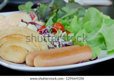 sausage , bread and  fresh vegetable salad on white dish