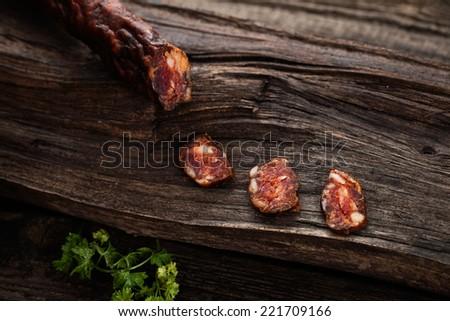Sausage. Dried Smoked Sausages Sliced on wooden Board. Chorizo sausage - stock photo