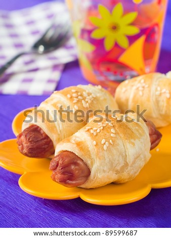 Sausage in dough for children breakfast, selective focus - stock photo