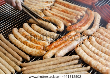 Sausage party. Barbecue large grill outdoors. Cookout bbq food. Big roasted pork german bratwurst, white polish kielbasa. Meat grilled meal. Street fast food. Tasty snack - stock photo