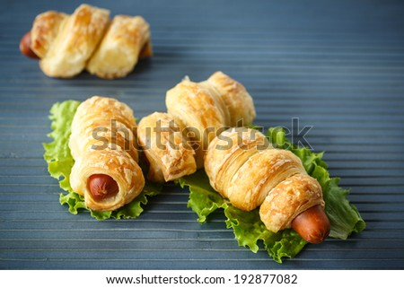sausage roll with lettuce on the table - stock photo