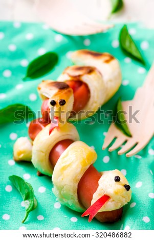 sausage rolls in the form of a snake for a children's holiday. selective focus - stock photo