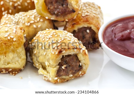Sausage rolls with tomato sauce or ketchup.  Puff pastry sprinkled with sesame seeds.