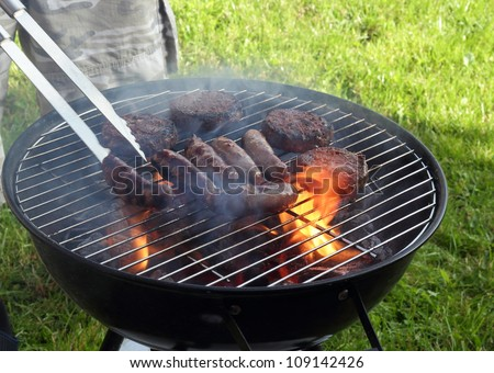 Sausages and burgers on a BBQ grill - stock photo