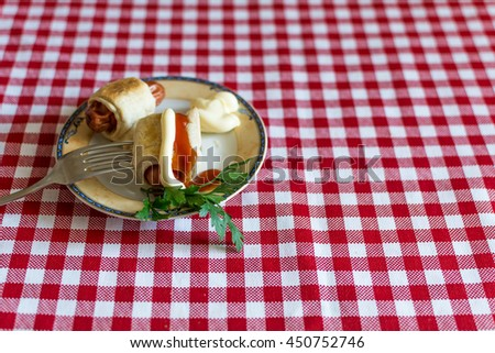 Sausages in dough ( Mini hot dog homemade ) with ketchup, mayonnaise and parsley on a plate. Sausage dough grilled furnace or in a furnace. - stock photo