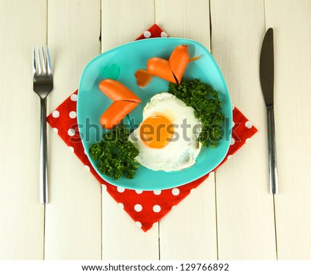 Sausages in form of hearts, scrambled eggs and parsley, on color plate, on wooden background - stock photo