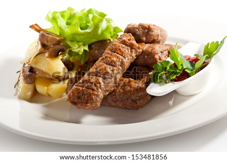 Sausages of Beef, Pork and Lamb Meat. Garnished with Potato and Green Salad Leaf - stock photo