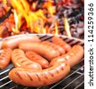 Sausages on a grill. In the background in bonfire. - stock photo