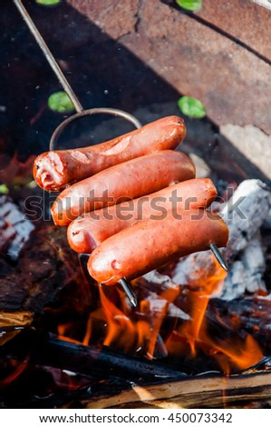 Sausages on a metal stick over the fire - stock photo