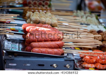 sausages on skewers in a street kiosk. Meat products in the menu on the counter Asian fast food restaurant. Thai traditional food on the street shop. Warm hot sausages on a stick - stock photo