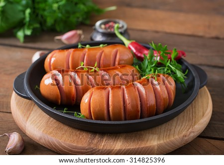 Sausages on the grill pan on the wooden background - stock photo