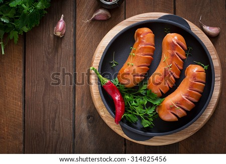 Sausages on the grill pan on the wooden background. Top view - stock photo