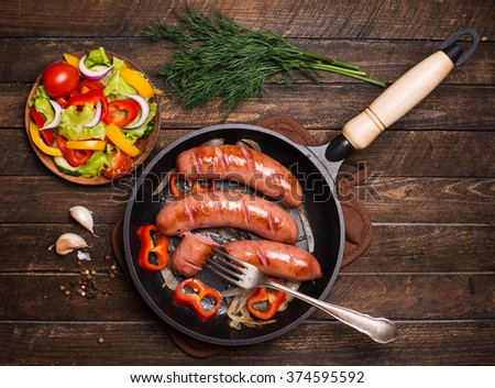 Sausages on the grill pan on the wooden background. Top view. Frying pan with fried sausage, vegetables and fork on a rustic wooden table.  - stock photo