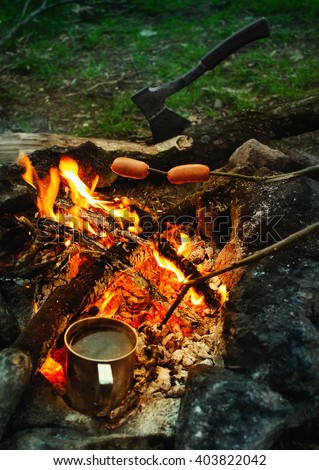 Sausages on the stick grilled in the fire. The scene with the fire, a metal mug with water, sausages on the twig and ax. - stock photo