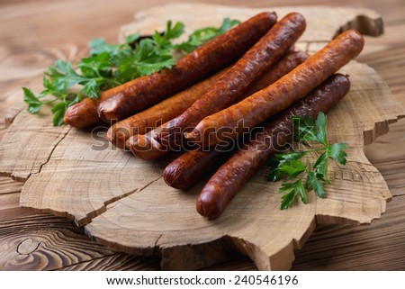 Sausages with parsley over rustic wooden background - stock photo