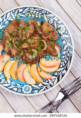 Sauteed chicken liver with apple and onion. View from above, top studio shot