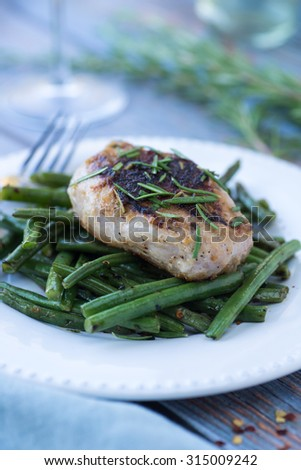 Sauteed pork chop with rosemary over spicy green beans - stock photo