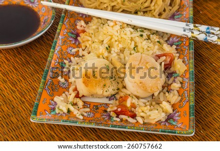 Sauteed scallops on bed of rice stir fry with Chinese noodles.  Served on Oriental design dishes with chopsticks and bowl of soy sauce against bamboo place mat background. - stock photo