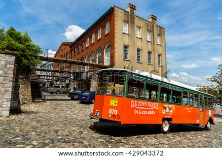 Savannah, GA USA - April 25, 2016: The Old Town Trolley with tourists visiting the popular Factors Walk along the Riverfront Plaza in the historic downtown district.