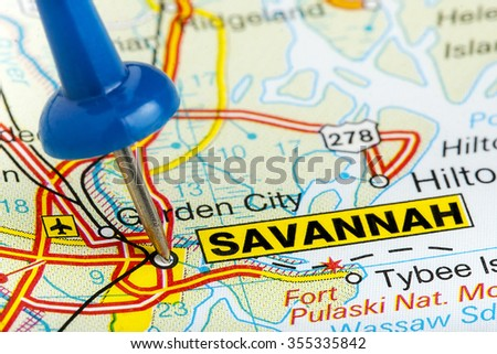 Savannah Georgia highlighted with blue push pin on atlas or map closeup - stock photo