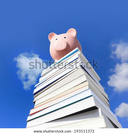 Save money by knowledge - pink piggy bank on stack Of books Against Blue Sky - stock photo