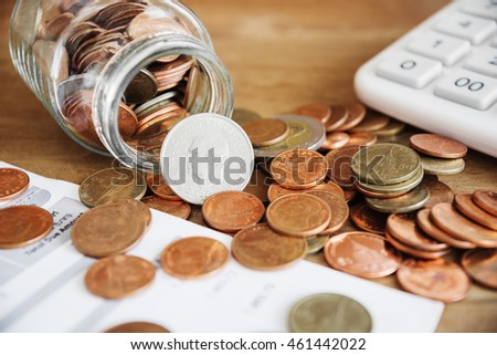 Save money for prepare in the future, Save money concept, Coins spilling out of a glass bottle with bill and calculator, Bill for income and expenditure and tax selective focus
